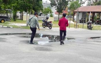 Dian (kanan) didampingi rekannya melangkahkan kaki keluar dari Mapolres Palangka Raya, usai melaporkan dugaan penggelapan sepeda motor, Jumat (26/8/2016). BORNEONEWS/BUDI YULIANTO