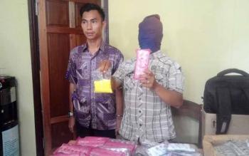 M Adnan, didampingi anggota Reskrim Polres Pulang Pisau menunjukkan zenit dan destro yang diambil dari Banjarmasin dan diedarkan di pasar-pasat kaget (pasar tumpah). BORNEONEWS/DJEMMY NAPOLEON