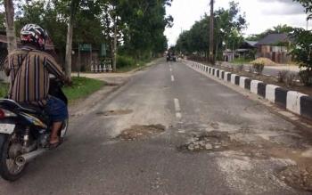 Pengendara sepeda motor melintas di jalan Natai Arahan, Minggu (25/9/2016). Jalan tersebut kondisinya memprihatinkan, banyak lubang menganga yang membahayakan keselamatan pengendara. BORNEONEWS/CECEP HERDI