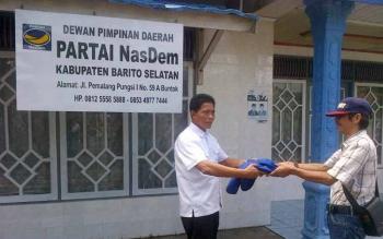 Mantan Sekretaris Partai Nasdem H Sadeli (kiri) menyerahkan atribut partai kepada salah satu staf di kantor Nasdem di Buntok Senin (26/9/2016). BORNEONEWS/PPOST/H. LAILY MANSYUR