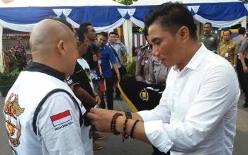 Bupati Kotim, Supian Hadi menyematkan pin keselamatan berlalulintas kepada warga Sampit pada acara ulang tahun Satlantas beberapa waktu lalu. BORNEONEWS/RAFIUDIN