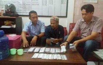 Dua orang anggota Satreskoba Polres Kotim meimpit tersangka penjual obat zenith carnophen, saat dilakukan ekspos di ruang narkoba, Rabu (28/9/2016). BORNEONEWS/HAMIM