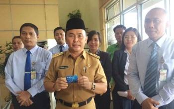 Gubernur Kalteng, Sugianto Sabran menunjukan kartu ATM Bank Kalteng miliknya di kantor Bank Kalteng Cabang Pangkalan Bun, Selasa (27/9/2016). Gubernur intruksikan Bupati untuk mencabut lahan yang bermasalah dari tangan investor. BORNEONEWS/CECEP HERDI