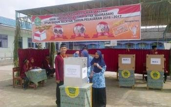 Proses Pemilihan Ketua Osis MTsN Buntok berlangsung. Seorang siswa saat memasukkan surat suara pada kotak suara yang dijaga petugas pemilihan. BORNEONEWS/PPOST/H. LAILY MANSYUR