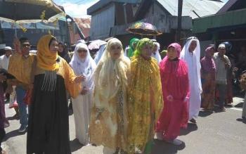 Jamaah haji Kabupaten Sukamara menjalani proses penyambutan, di halaman Masjid Al-Aqso Sukamara, Kamis (29/9/2016). Kedatangan 10 jamaah haji diiringi alunan sholawat Nabi dan penamburan beras kuning. BORNEONEWS/NORHASANAH