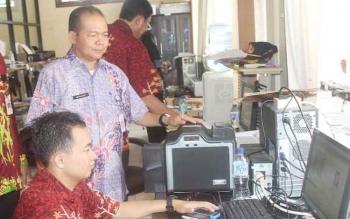 Kepala Dinas Kependudukan dan Pencatatan Sipil Kotim, Marjuki memantau proses pencetakan e-KTP. BORNEONEWS/RAFIUDIN