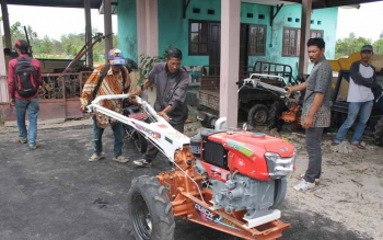 Petani mendorong hand tractor yang disumbangkan pemerintah, di Dinas Pertanian Peternakan Penyuluhan dan Ketahanan Pangan Kotim. BORNEONEWS/RAFIUDIN