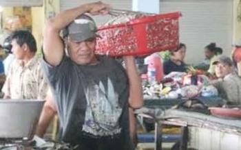 Seorang penjual ikan di Pusat Perbelanjaan Mentaya (PPM) Sampit sedang membawa ikan dagangannya, sebelum diampar di kios, beberapa waktu lalu. BORNEONEWS/HAMIM