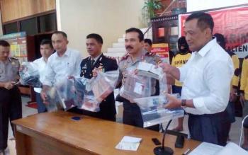 Kapolda Kalteng Fakhrizal mengangkat barang bukti berupa uang tunai hasil perampokan. BORNEONEWS/HABIBULLAH