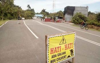 Tampak Plang peringatan yang dipasang DPU kabuapaten, menjelaskan adanya kondisi jalan beraspal yang amblas di Jalan Yos Sudarso, Nanga Bulik. BORNEONEWS/HENDI NURFALAH