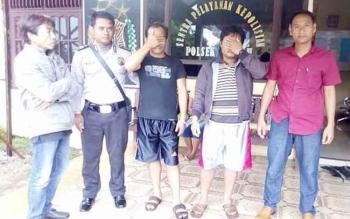 Dua tersangka pembunuh di Desa Bawan, Kecamatan Banama Tingan, Kabupaten Pulang Pisau menutup wajah saat dibawa dari Polsek Tewah menuju Polres Pulang Pisau, Kamis (6/10/2016) pagi. BORNEONEWS/JAMES DONNY
