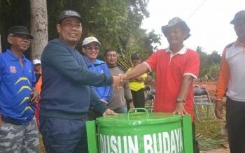 Bupati Katingan, Ahmad Yantenglie menyerahkan tong sampah kepada Ketua Rt 6, Dusun Betung Syamin Sinel pada acara Jumat Beriman, Jumat (7/10/2016). BORNEONEWS/ABDUL GOFUR