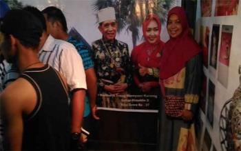 Salah satu pengunjung, Sri Hasyim, berfoto dengan latar belakang backdrop Raja Gowa ke-37, Andi Maddusila Daeng Mannyonri Karaeng Sultan Alauddin II, di Istana Kuning, Pangkalan Bun, Selasa (11/10/2016). BORNEONEWS/NAZIR AMIN
