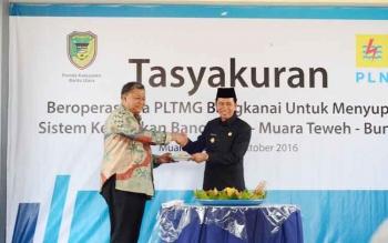 Bupati Barito Utara, H Nadalsyah (kanan) menyerahkan potongan tumpeng kepada Direktur Bisnis Regional Kalimantan, Joko R Abumana pada Tasyakuran beroperasinya sistem kelistrikan Bangkanai, Rabu (12/10/2016). BORNEONEWS/RAMADANI