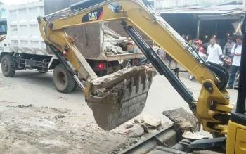Satpol PP) Kota Palangka Raya menggusur pedagang kaki lima (PKL) di Jalan Jawa, Pasar Besar, dengan alat berat, Rabu (12/10/2016). PKL dinilai bandel lantaran masih berjualan di atas drainase, dan bahu jalan. BORNEONEWS/BUDI YULIANTO
