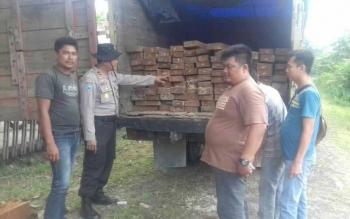 Anggota Polsek TSG dan Pulau Malan saat mengamankan dua truk pengangkut kayu ilegal di Desa Tumbang Tanjung Kamis (13/10). BORNEONEWS/ISTIMEWA