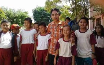 Anggota Dewan Perwakilan Rakyat Daerah (DPRD) Kabupaten Gunung Mas Herbert Y Asin menyempatkan berfoto bersama para pelajar Sekolah Dasar Negeri (SDN) 1 Kurun ketika berkunjung ke sekolah tersebut, Jumat (14/10/2016). BORNEONEWS/EPRA