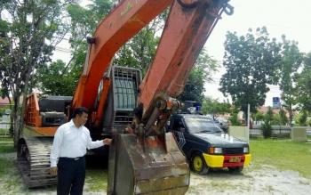 Kasat Reskrim Polres Palangka Raya AKP Erwin T H Situmorang menunjukkan excavator yang diamankan di Polres Palangka Raya, Senin (17/10/2016). BORNEONEWS/BUDI YULIANTO