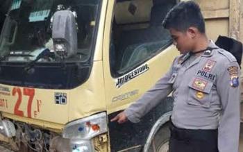 Seorang anggota polisi sedang menunjukkan kondisi depan truk yang menabrak pengendara motor hingga tewas. BORNEONEWS/HAMIM