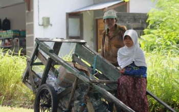 Irmawati berkerudung putih saat membantu ayahnya mencari plastik bekas di sepanjang jalan Kuala Pembuang, setiap hari. BORNEONEWS/PARNEN