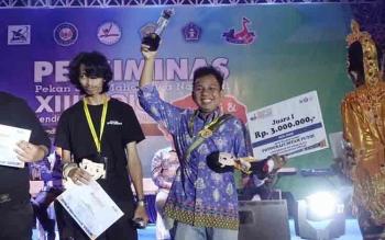 Mahasiswa Universitas Palangka Raya, M Fahmi Idris, usai penyerahan piala Juara I tangkai lomba fotografi hitam putih (BW) pada Pekan Seni Mahasiswa Nasional di Kendari, baru-baru ini.