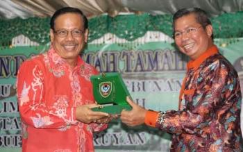 Kepala Dinas Perkebunan Kalimantan Tengah, Rawing Rambang (kiri) menerima plakat daerah yang diserahkan Bupati Seruyan Sudarsono, Senin (17/10/2016) malam. Rawing memaparkan perkembangan perkebunan di Kalteng. BORNEONEWS/PARNEN
