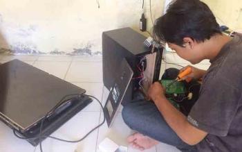 Penyedia jasa perbaikan alat elektronik, Topik, warga Kelurahan Madurejo Pangkalan Bun, memperbaiki televisi konsumen, Selasa (18/10/2016). Ia kebanjiran order pascabadai guntur pekan lalu. BORNEONEWS/CECEP HERDI