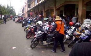Seorang juru parkir merapikan kendaraan roda dua yang diparkir di Jalan Iskandar Sampit. Bupati Kotim, Supian Hadi, Kamis (20/10/2016), perintahkan berantas pungli perparkiran. BORNEONEWS/RAFIUDIN
