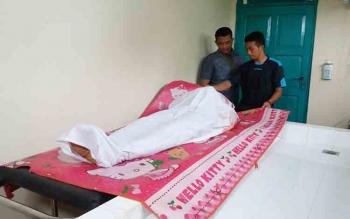 Dua orang petugas kamar mayat sedang melakukan pemeriksaan terhadap luka tembak yang dialami Edmondus, Kamis (20/10/2016). BORNEONEWS/HAMIM