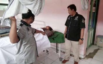 Kasat Reskrim Polres Kapuas AKP Wiwin JS (kanan) menunjukkan jenazah Nur Siati (40) saat berada di kamar mayat RSUD Kapuas. BORNEONEWS/PPOST/SRI HAYATI