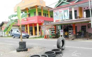 Warga Jalan Katunen Kasongan menanam batang pisang di tengah jalan yang rusak, Minggu (23/10/2016). Mereka kesal karena jalan rusak itu tak kunjung diperbaiki. BORNEONEWS/ABDUL GOFUR