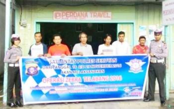 Dua anggota Satlantas Polres Seruyan bersama sejumlah warga Kuala Pembuang tengah membentangkan spanduk berisi imbauan jadwal pelaksanaan Operasi Zebra Telabang 2016 pada 16-29 November 2016. BORNEONEWS/PARNEN
