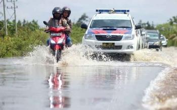Luapan air Sungai Kahayan dan Rungan menyebabkan jalan Trans Kalimantan poros tengah, di Desa Sungai Lais, Kecamatan Bukit Rawi, Pulang Pisau tergenang banjir sepanjang 2,5 kilometer, dengan kedalaman 30 Cm, Senin (7/11/2016). BORNEONEWS/DOK