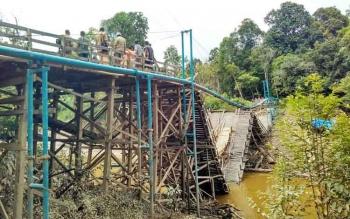 Jembatan konstruksi kayu ulin sepanjang 63 meter, yang berada di Desa Benao ambruk akibat pengaruh abrasi sungai yang terjadi saat musim hujan, Selasa (8/11) pagi. (PPOST/AGUS SIDIK)