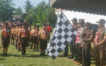 Camat Katingan Hilir, Ardiansyah mengibarkan bendera tanda dimulainya lomba gerak jalan pramuka di Lapangan Gagah Lurus Kasongan, Sabtu (12/11/2016). BORNEONEWS/ABDUL GOFUR