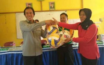 Anggota Komisi IV DPR RI, H. Hamdhani menyerahkan bantuan bola volly kepada Kepala Sekolah SMKN 1 Sukamara, Sarce Sisyoan disaksikan para siswa di Aula SMKN 1 Sukamara, kemarin. BORNEONEWS/NORHASANAH