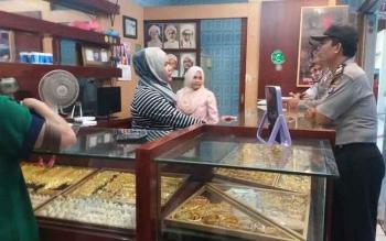 Pejabat Sementara Polsek KPM Aiptu Ragil sedang berbincang dengan penjual toko emas di PPM Sampit. BORNEONEWS/HAMIM