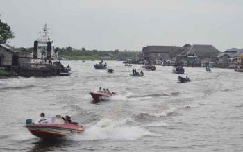 Speedboat jurusan Sukamara (Kalimantan Tengah) – Kecamatan Manis Mata, Kabupaten Ketapang, Kalimantan Barat, saat melintas di Sungai Jelai. Dalam kondisi cuaca buruk di musim hujan, motoris diimbau agar berhati-hati. BORNEONEWS/NORHASANAH