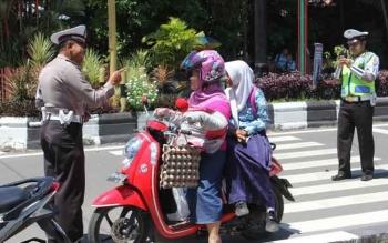 Anggota Polantas memberhentikan pengendara sepeda motor yang berboncengan namun penumpang tak menggunakan helm, beberapa waktu lalu. Polres Kotim menggelar Operasi Zebra, mulai Rabu (16/11/2016). BORNEONEWS/M. HAMIM