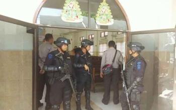 Sejumlah anggota brimob berpakaian lengkap dengan senjatanya sedang berjaga-jaga di depan pintu masuk salah satu gereja di Kota Sampit. BORNEONEWS/HAMIM