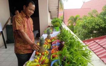 Sekretaris Daerah Kotim, Putu Sudarsana memperlihatkan buah-buahan dan sayur-sayuran hasil produksi lokal.