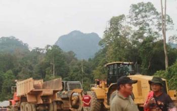 Alat berat milik PT Dwima Group yang membantu membuat jalur pendakian ke kaki bukit Tantan Samatuan, yang puncaknya kelihatan dari kejauhan.
