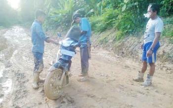 Warga Desa Karendan yang menuju kota Muara Teweh harus berjuang di antara kubangan lumpur di jalan menuju desa, karena belum ada perbaikan. BORNEONEWS/RAMADANI