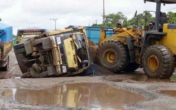 Terlihat truk pengangkut karnel terbalik di JL HM Arsyad Km 22, yang kondisi jalannnya sedang rusak, dan berlubang cukup dalam. BORNEONEWS/HAMIM