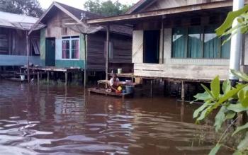 Seorang warga yang rumahnya tergenang banjir, mencuci pakaian di depan rumah. Aktivitas warga di empat desa di Kecamatan Cempaga Hulu lumpuh total, Minggu (20/11/2016). BORNEONEWS/RAFIUDIN