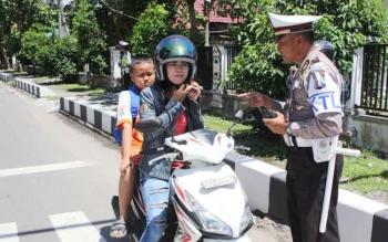 Anggota Satlantas Polres Kotim sedang memberikan wejangan kepada pengendara sepeda motor yang tidak mengancingkan helmnya, di Sampit, Sabtu (19/11/2016). Operasi Zebra juga akan menyasar wilayah kecamatan. BORNEONEWS/M. HAMIM