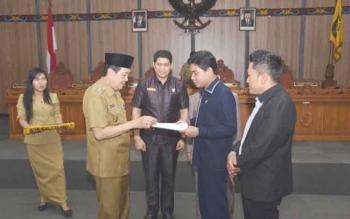 Ketua DPRD Kotim, Jhon Krisli (dua kanan) menyerahkan hasil pembahasan Raperda kepada Wakil Bupati Kotim, M Taufiq Mukri, disaksikan Ketua Baleg Dadang H Syamsu (kanan). BORNEONEWS/M. RIFQI