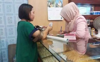Seorang pembeli sedang menghitung uangnya untuk membeli emas di salah satu toko di Pusat Perbelanjaan Mentaya (PPM) Sampit, Senin (21/11/2016). BORNEONEWS/M. HAMIM