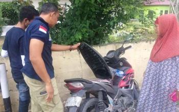 Polisi memeriksa jok sepeda motor tempat Ardiana (43), menyimpan uang Rp21 juta. Uang itu raib saat motornya diparkir di depan toko alat pancing, Jalan Pangeran Antasari, Pangkalan Bun, Selasa (22/11/2016). BORNEONEWS/CECEP HERDI