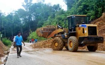 Dinas PU Barut langsung melakukan langkah cepat dengan menurunkan alat berat jenis dozer untuk memindahkan tumpukan tanah longsor ke samping badan jalan, Selasa (22/11) siang.(BORNEONEWS/AGUS SIDIK)